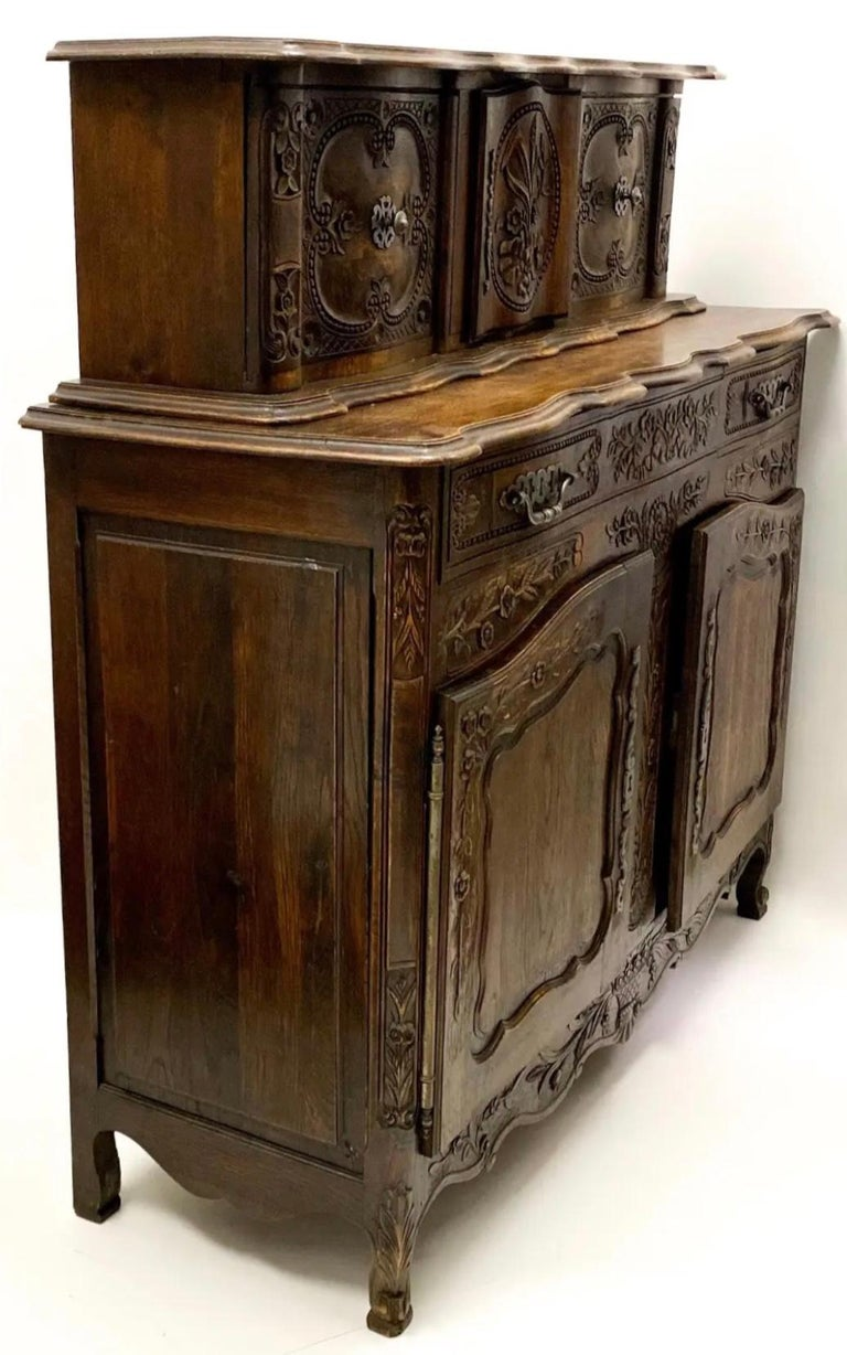 This 19th century Louis XV style oak cabinet has amazing carved details, original pewter hardware and a unique tambour style removable top. The top could be used separately as a wall mounted cabinet. It is a special piece, and does include a