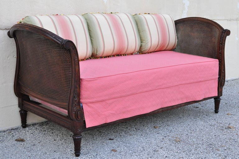 19th century French Louis XVI carved walnut & cane daybed sofa with custom mattress and pillows. Item features double cane panels, custom mattress, custom support, and stunning custom silk upholstered double sided pink, gold, and green 12
