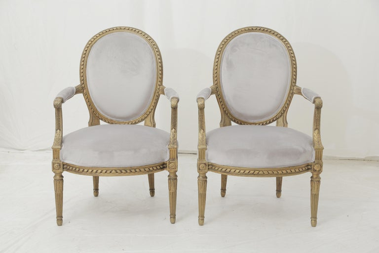 Set with a loveseat and a pair of armchairs made of giltwood (beech). French Louis XVI Style, has been recently reupholstered in a light grey suede fabric. Good condition, some light gaps on the sculpture and the layer of gilding on the back. Tight