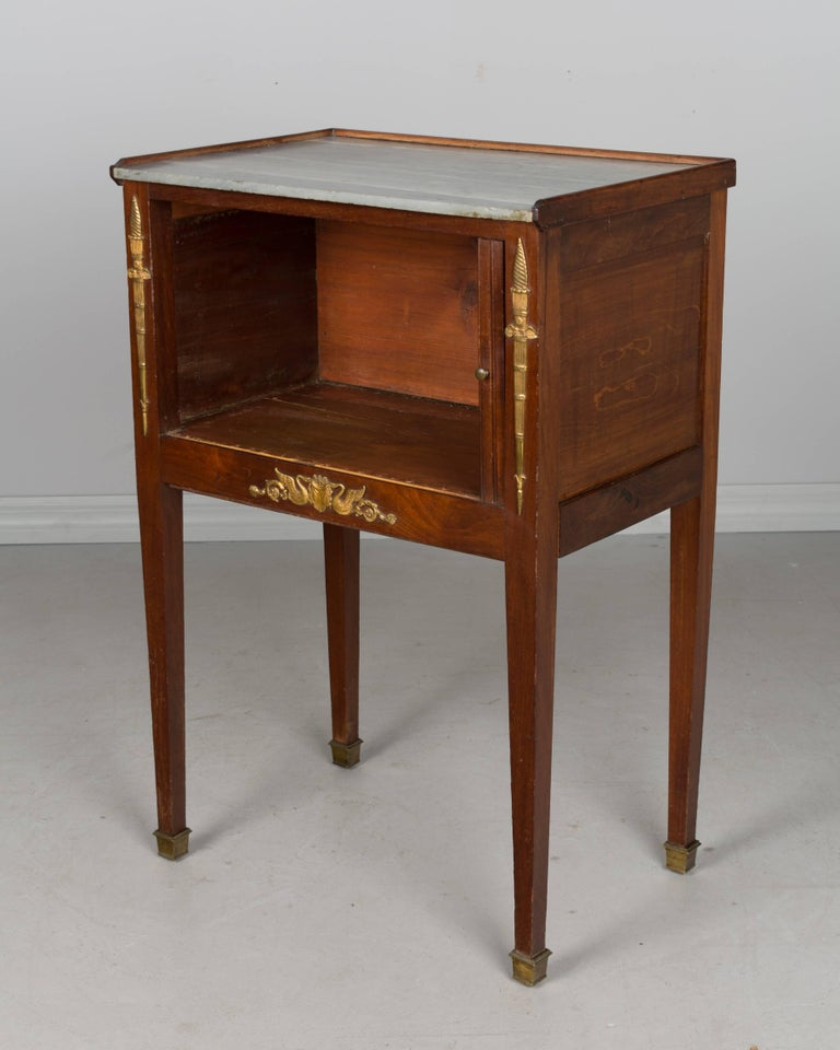 A 19th century French Louis XVI style side table with tambour door and grey marble top. Made of solid walnut with pine as a secondary wood. There is a small hidden dovetailed drawer that pulls out on the right side. Original bronze hardware. Please