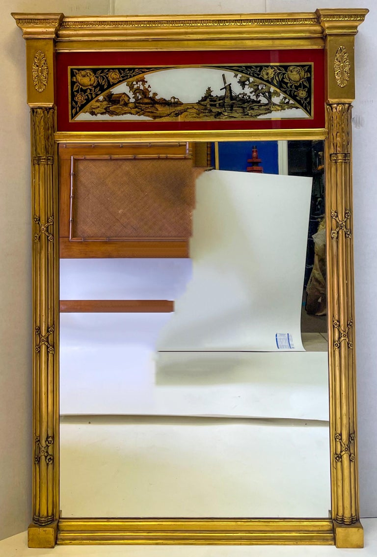 This is an exceptional French water gilt trumeau mirror with neoclassical styling. The panel is eglomise with a pastoral scene in a deep red, black and gilt. It dates to the late 19th century and is in very good condition.