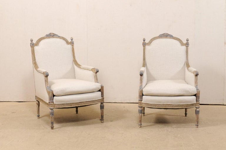 A French pair of occasional bergère chairs from the 19th century, with new upholstery. This antique pair of Louis XVI style armchairs from France each features a beautifully carved arched back-rail with foliage crest at center, a prominent pair of