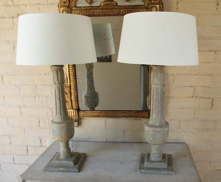 A beautiful pair of 19th c. French balustrades converted to table lamps with braided French cords. The patina is a very neutral aged gray. The lampshade is handmade in Belgium of fine linen and has a high quality gold foil inner lining. The lining