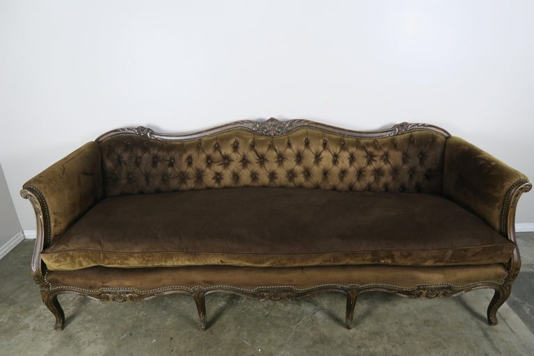 19th century French carved walnut sofa that stands on eight cabriole shaped legs. The sofa is beautifully detailed with hand carved flowers and acanthus leaves throughout. The sofa back is all tufted with smooth arms and down filled loose seat