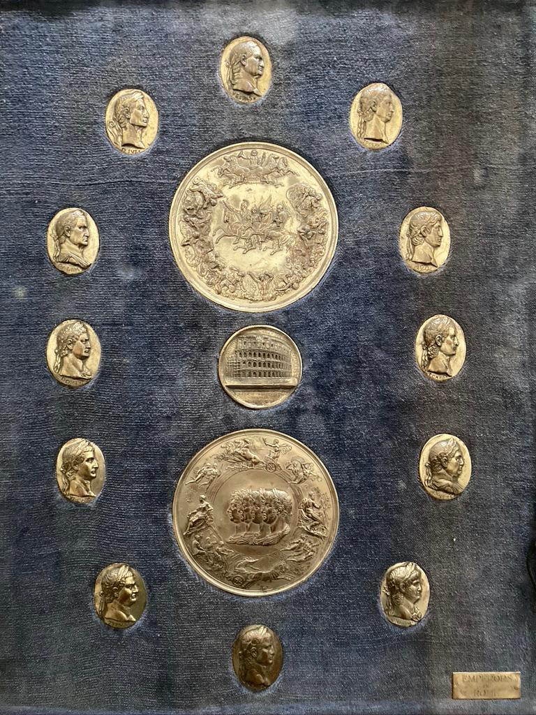 An interesting and unusual Grand Tour collection of silvered bronze cameo medallions of 12 Roman Emperors, 19th century. The 12 Caesars surrounding a pair of large medallions, one depicting four busts wearing laurels, the other with various