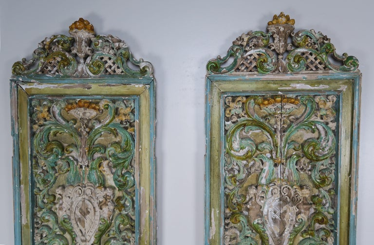 Pair of 19th century Italian carved and painted panels. The intricate carving depicts urns with swirling acanthus leaves throughout. Beautiful shades of greens, blues and golds. Ready to hang.