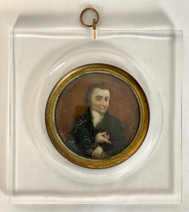 An early 19th century Italian portrait miniature of a gentleman in a black coat pointing downward. Set in a later Lucite frame.