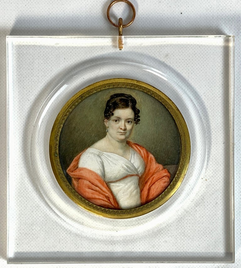 A beautifully painted early 19th century Italian portrait miniature of an elegant woman in white dress with coral shawl. Recently framed in Lucite frame.