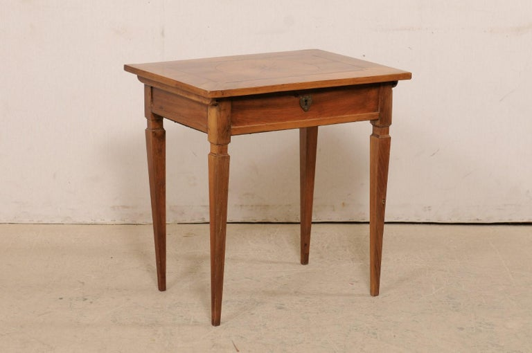 An Italian smaller-sized writing desk with storage hidden beneath top from the 19th century. This super cute desk, or occasional table from Italy, is adorn with beautiful inlay on the top with a circular medallion with flower head at it's center and