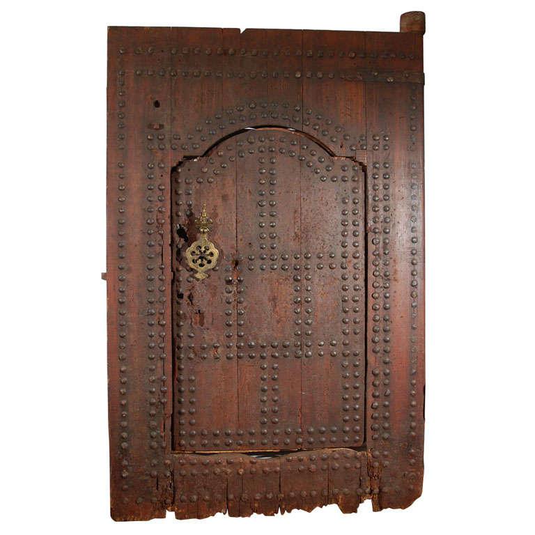 Antique massive handcrafted Hispano Moresque studded doorway, incredible work, very heavy authentic Moroccan door. One door inside a larger door. 19th century or before studded wood large authentic Moorish door from Marrakech. Indoor or outdoor