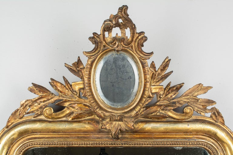 A 19th century Louis Philippe style giltwood mirror with oval mirrored crest surrounded by gilded leaves. Curved top corners, bright gilt with incised decoration, bead border, bottom corner decoration. Original mirror. Losses and repairs to the the