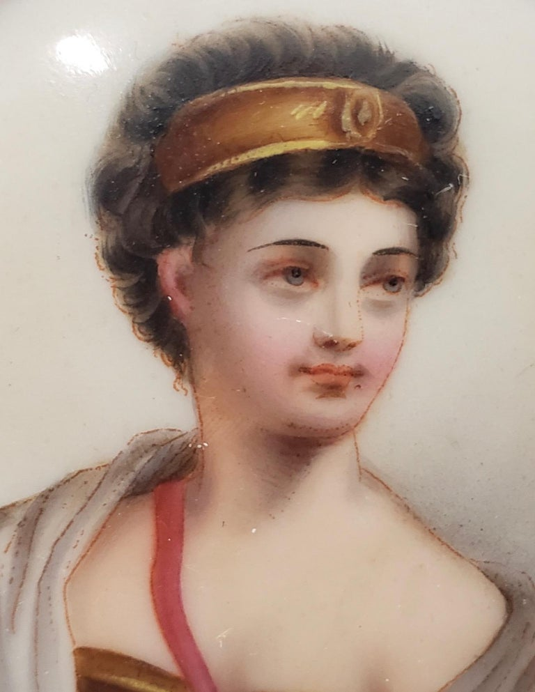 Fine 19th century miniature portrait on porcelain of a beautiful young woman  A finely detailed portrait of a young woman with short auburn hair and a gold head band.  The porcelain portrait is housed in a gilded brass frame with enamel paint