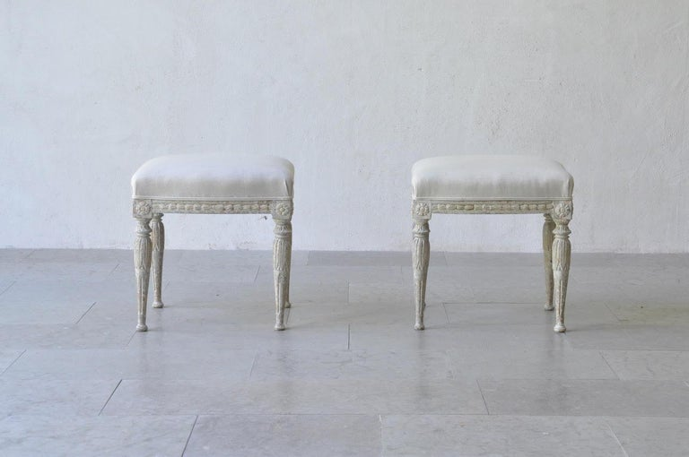 A beautiful pair of Swedish footstools from the Gustavian period. These stools have been hand-scraped to reveal the original paint. There are carved bell flowers on the seat frame with rosettes on the corner posts and acanthus leaves on tapered
