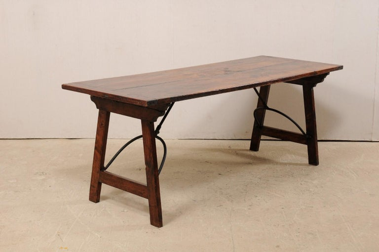 A Spanish table with nicely designed folding legs from the 19th century. This antique table from Spain features a rectangular-shaped top, approximately 6.75 ft in length, which is raised upon a pair of sawhorse style legs. Each set of legs is