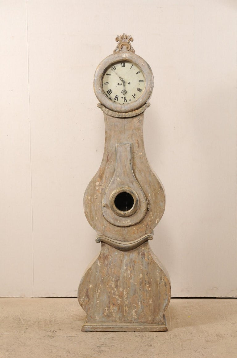 A 19th century Swedish Fryksdahl clock with shapely body and carved crown. This antique Fryksdahl clock from Sweden has a raised crest, carved in c-scroll with splaying foliage rising out of the top, a rounded head, and diamond and floral carved