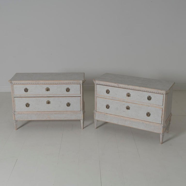 A pair of Swedish commodes in the Gustavian style with dentil molding around the top. Chalky antique ivory paint. Two large drawers, canted corner posts, and tapered legs. Two keys.