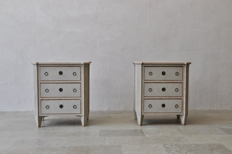 A beautiful pair of Swedish bedside chests in the Gustavian style. Three drawers, brass hardware, canted and fluted corner posts, and tapered legs. Original locks with keys.
