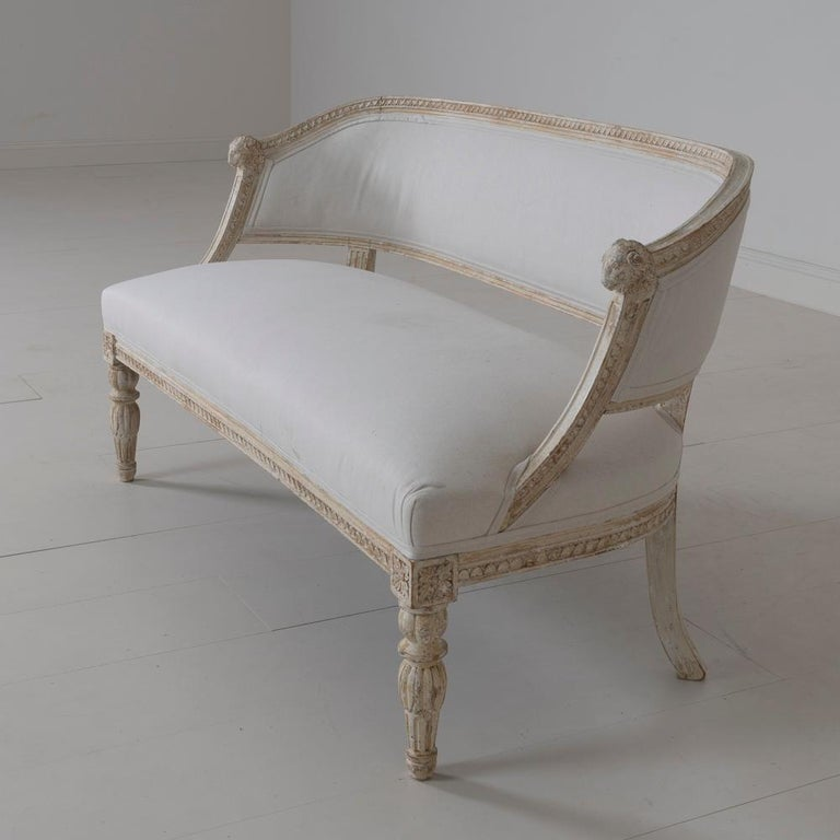 A rare 19th century Swedish barrel back sofa settee in the Gustavian style, newly upholstered in linen, circa 1880. Hand scraped to reveal the original paint. The frame has a craved egg and dart detail, while the front legs are adorned with lotus