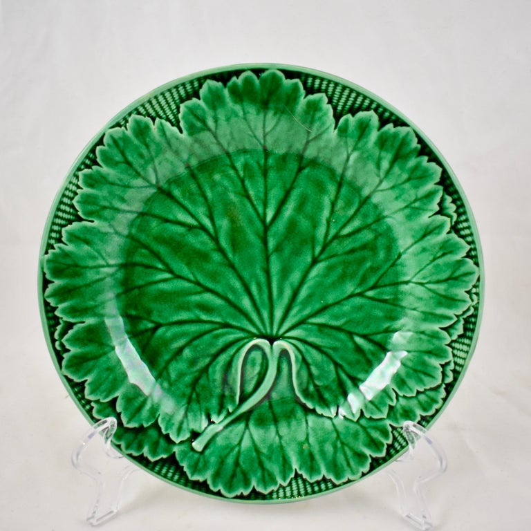 A Majolica green glazed plate, from the English firm of Wedgwood. A Classic mold showing a single large cabbage leaf against a basket-weave patterned rim. The deep green glaze pools beautifully into the dimensional mold work. Multiple plates are