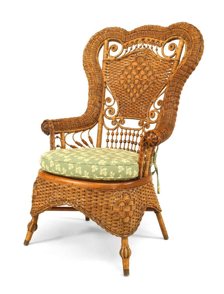 Bearing the label of the American company Whitney Reed Chair Co., this nineteenth century wicker armchair features an elaborate high back with scroll and spindle designs, as well as a a cushion upholstered in a light green ivy textile.