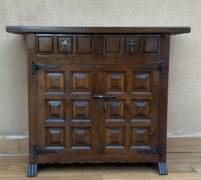 From Northern Spain, constructed of solid walnut, the rectangular top with molded edge atop a conforming case housing two drawers over two doors, the doors paneled with solid walnut, raised on a plinth base.