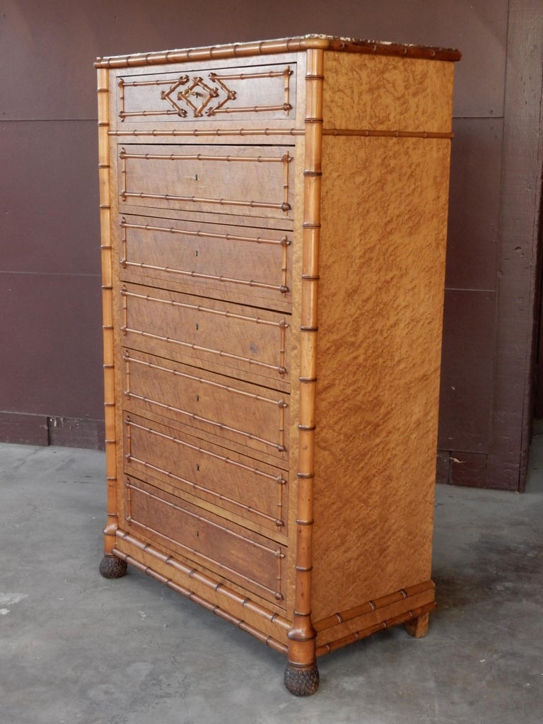 Exceptional 7-drawer, locking Semainier chest from France. From the mid-19th century Aesthetic Movement era. Faux bamboo detail over gorgeous bird's-eye maple burl veneer. Solid oak construction. Bamboo stem front legs tapper to a realistic, hand