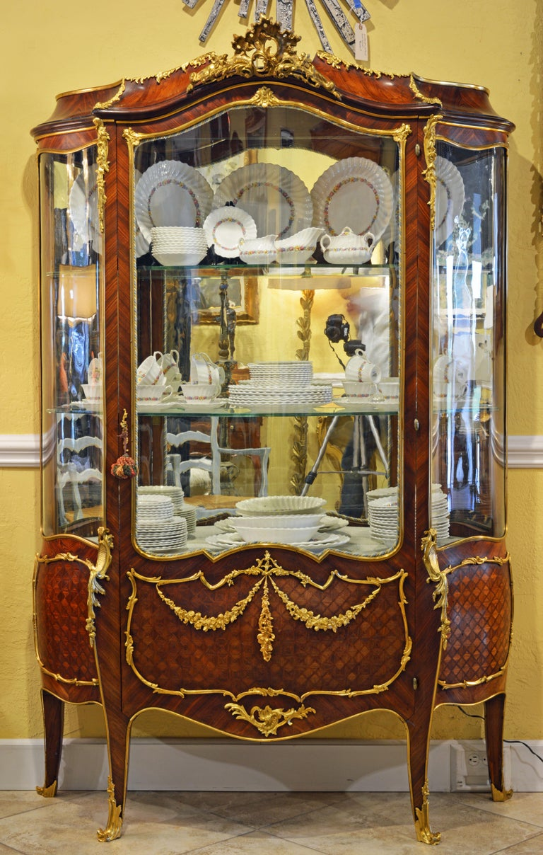 This magnificent French Louis XV style vernis martin vitrine or display cabinet features a kingwood and satinwood parquetry body adorned by richly detailed ormolu or gilt bronze mounts in the form of scrolls, leaf work and garlands creating an