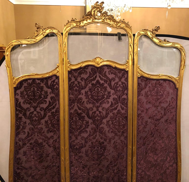 Fine Louis XV style giltwood three fold screen with original glass panels newly upholstered in a cut velvet amethyst color fabric, French, 19th century.   SXX