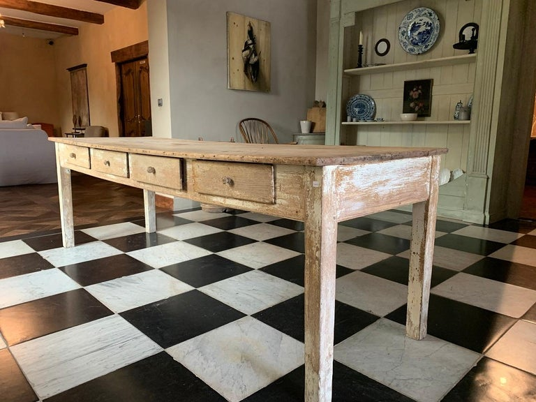 A early 19th century French oak and poplar farmhousetable. The supports with original white paint remains and the top in naturally bleached poplar. 4 Drawers on one side and panneling on the other. The top slightly bend.