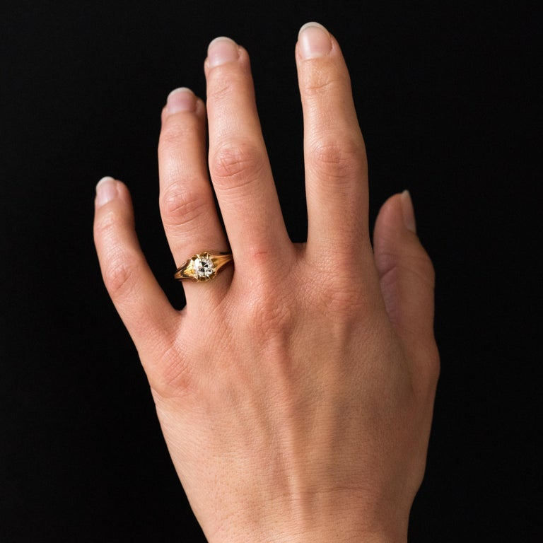 Ring in 18 karat yellow gold, eagle's head hallmark. This ring is adorned on the top with an antique brilliant- cut diamond, set with claws. It is supported on both sides of two throats that go down to the base of the ring. Total weight of the