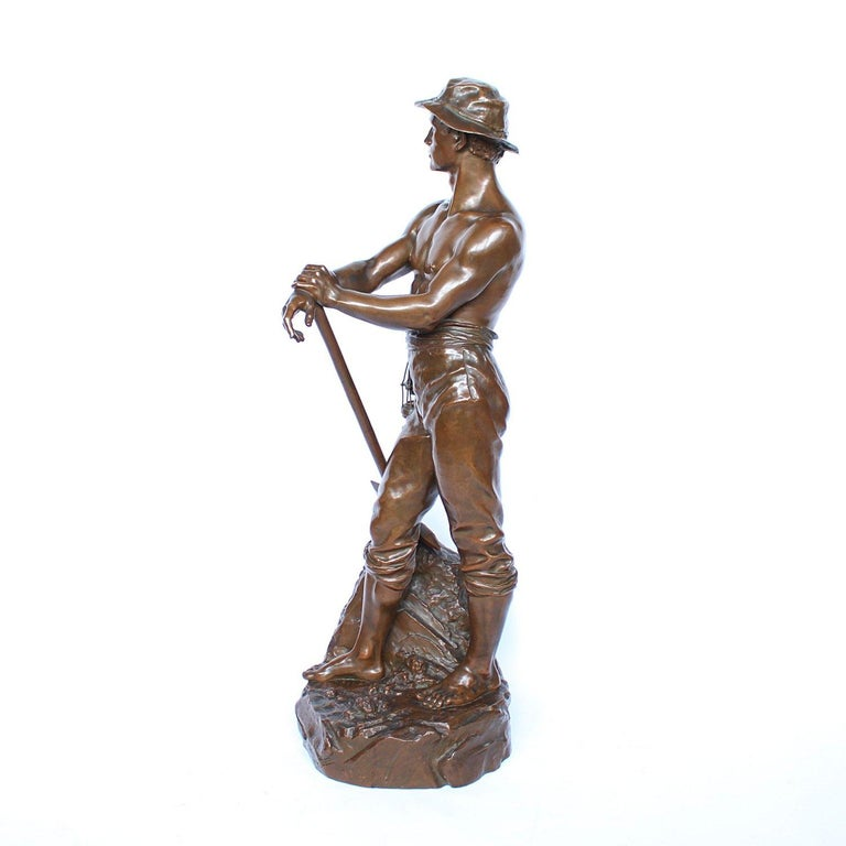 A large, 3ft tall bronze figure of a miner standing bare chested on an integral naturalistic base holding a pickaxe and a miner's lamp. Inscribed 'Mineur par Levy Salon des Beaux Arts', signed 'CH LEVY' and with the inscription: 'Bronze Garanti Au
