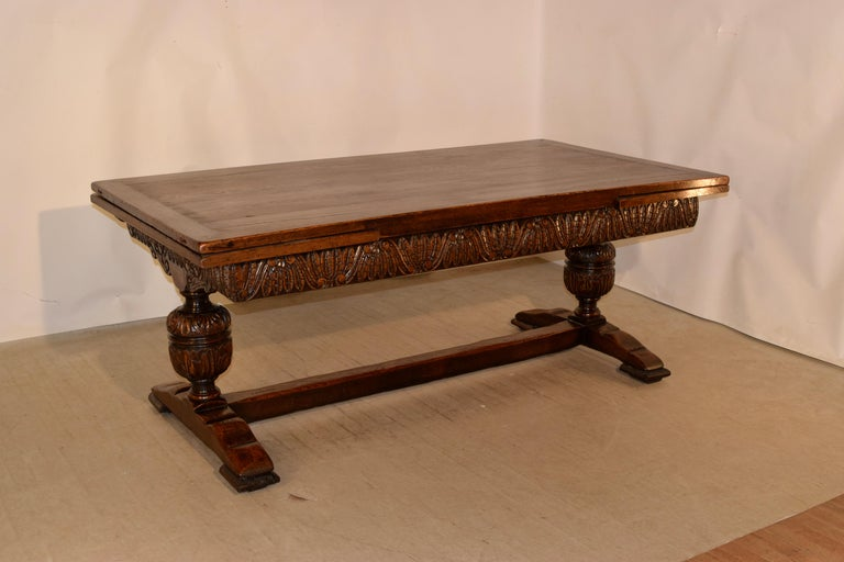 19th century massive oak table from England with draw leaves. The top is banded and has two leaves which draw out for an extended length of 120 inches. The top is supported on a trestle base, which has a wonderfully hand carved decorated apron and