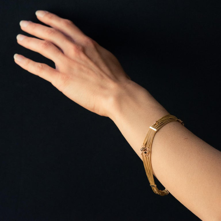 Bracelet in 18 karat rose gold. Lovely antique bracelet, it consists of 8 fine column link chains interspersed with small gold cubes. Three gold bars ensure the stability of the bracelet. The clasp is a spring ring. Total length: about 21 cm, width
