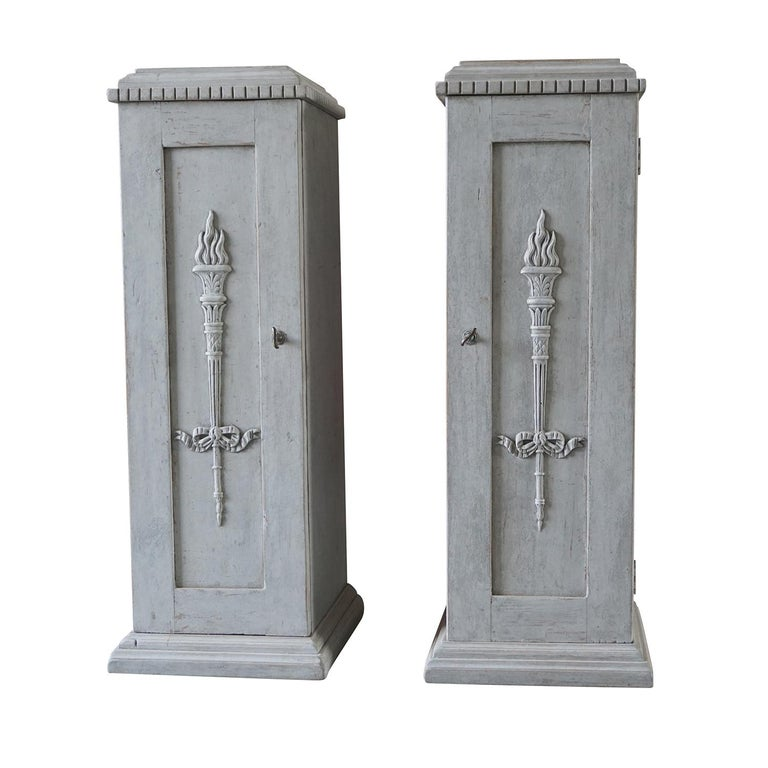 An unusual pair of Swedish side cabinets made of grey painted pinewood with one door and keys, featured inside with two white front drawers. The hand carved pedestals are in good condition and detailed in the neoclassical Greek style with their