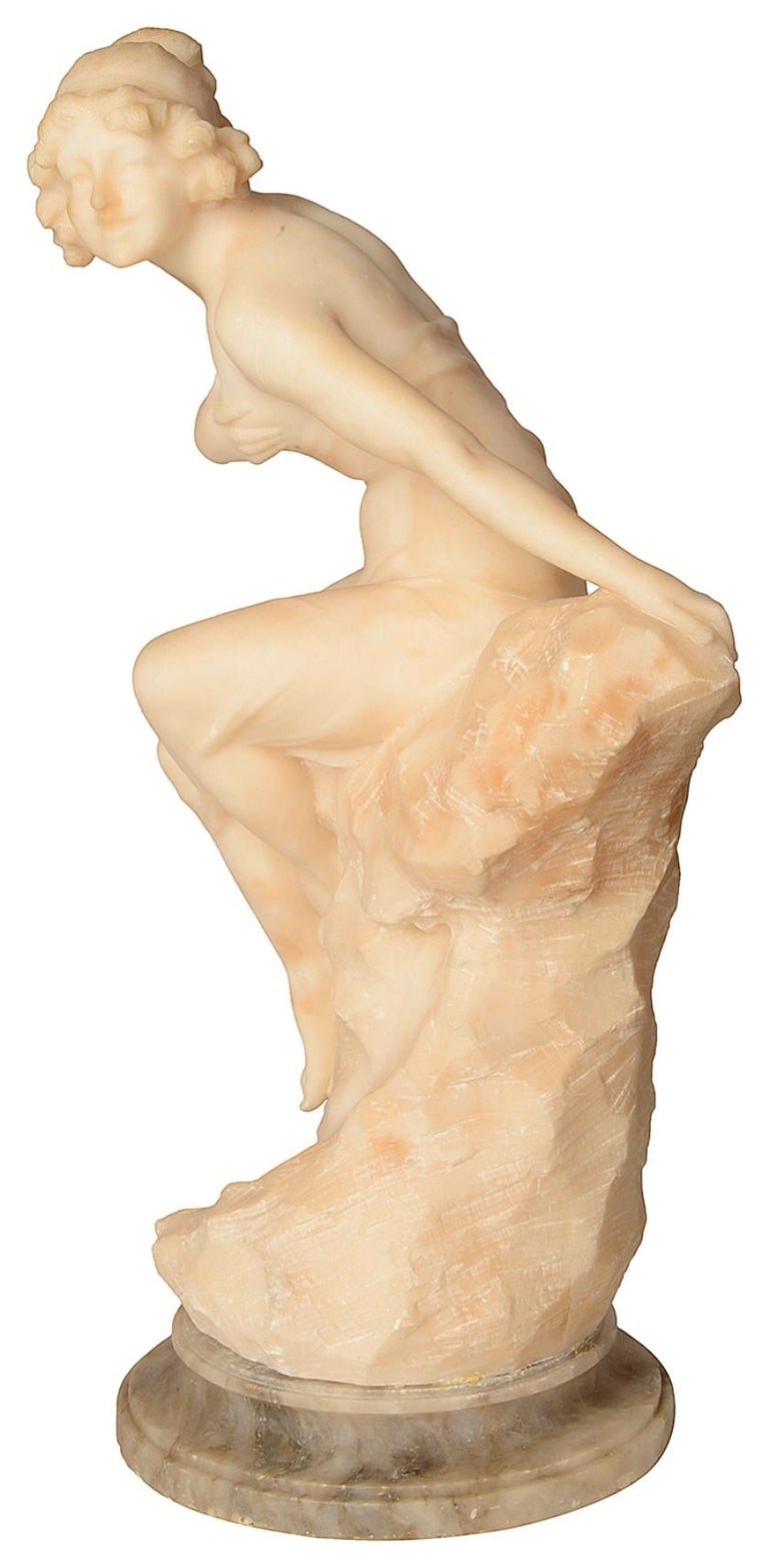 A good quality 19th century alabaster statue of a semi nude young girl sitting on a rock.