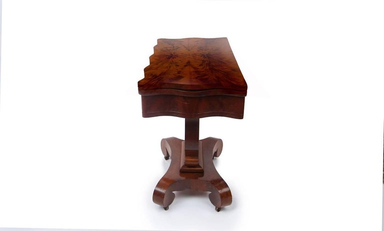 Handsome Empire card or tea table with centre pedestal in mahogany and matchbook flame mahogany. Hinged top opens to reveal compartment and pivots to become square table. Scalloped edge top and frieze supported by bold harp base and scroll legs with