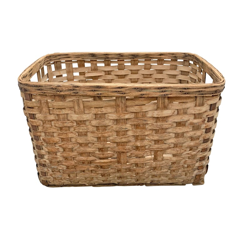 A large 19th century American oak splint shipping basket with a heavy double-banded rim, iron reinforcements on each corner, and two wooden runners across the bottom, all for added stability in shipping. Perfect for firewood, dogs toys, or anything