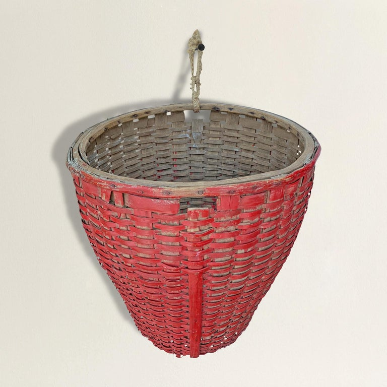 A fantastic 19th century American red painted oak splint round gathering basket with a tapered asymmetrical form making it perfect for hanging on a wall. Found in Western Massachusetts.