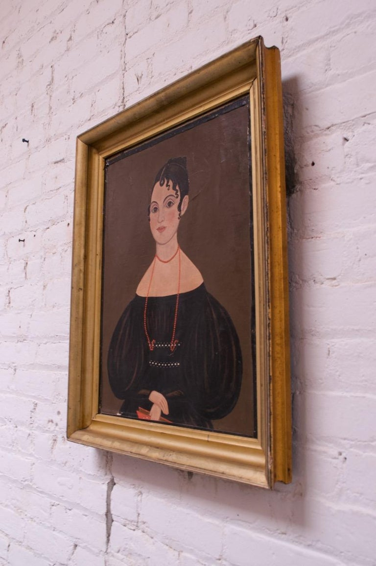 Folk Art oil painting depicting a seated lady, circa mid-late 19th century. Details like the exaggeratedly long neck are distorted, revealing a naive perspective. A nice period example in the folk art style.