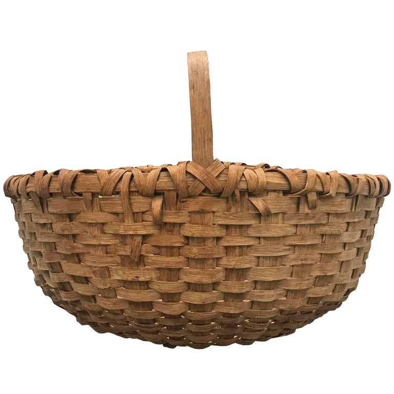 A large 19th century American splint oak gathering basket with one long bent-oak handle, a double banded rim, and a large belly. Found in New England.