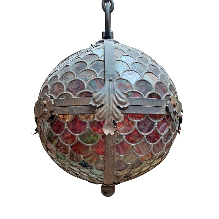 A fantastic late 19th century large-scale American stained glass orb pendant light fixture with the most incredible scale pattern. When fully illuminated, the color begins at the bottom with shades of deep emerald green and slowly fades to a