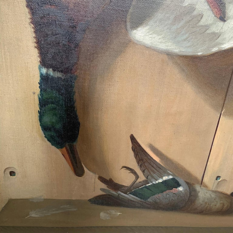 A wonderful 19th century American oil on canvas trompe l'oeil hunt painting depicting a large mallard duck hanging by a string, and a small teal duck with a few loose feathers lying on a shelf. Signed and dated,