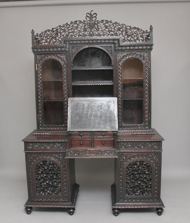 19th century Anglo-Indian hardwood bookcase desk, the base having two pedestals on turned feet, each pedestal with a heavily carved and pierced fret door which opens to reveal three drawers, above the pedestals is a section with two drawers flanking