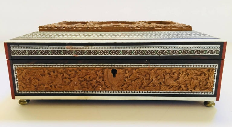 19th century Anglo-Indian wooden box, bone and sadeli mosaic box fitted with various compartments finely hand-carved with the Taj Mahal. The interior with removable hand-carved eight-lidded compartments, the front cover has a mirror, the whole