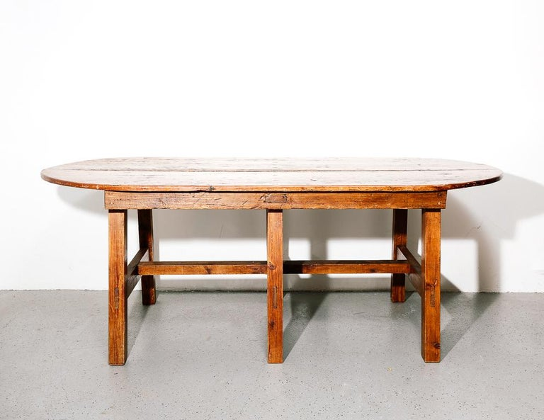 Large early American farmhouse dining table. Oval top and chunky squared base. Polished wax finish.