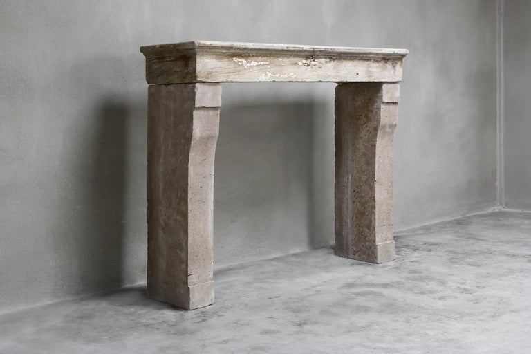 Beautiful sober antique fireplace from the 19th century. A fireplace of French limestone with a straight top and slightly bent legs. The color nuance is warm and there is a beautiful patinae on the fireplace. This fireplace is ideal for rural or