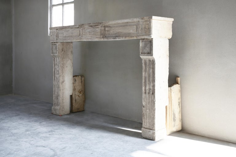 Beautiful French limestone antique fireplace from the 19th century. This fireplace is in the style of Louis XVI. It is a straight model with beautiful lines and cannelures on the legs. The color scheme is warm and adds atmosphere to your home.
