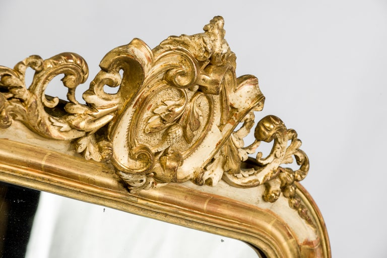 This wonderful antique French mirror has the typical rounded upper corners of a Louis Philippe mirror. The frame is enriched with acanthus ornaments and a beautiful ornate crest on top.  The frame was partially gold leaf gild and gold paint gilt.