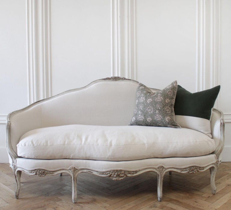 19th century antique French Louis XV style sofa Painted in a light oyster white, with subtle distressed edges, and finished in an oyster antique glazed patina. Upholstered in 100% pure organic Libeco linen in light natural. A large overstuffed