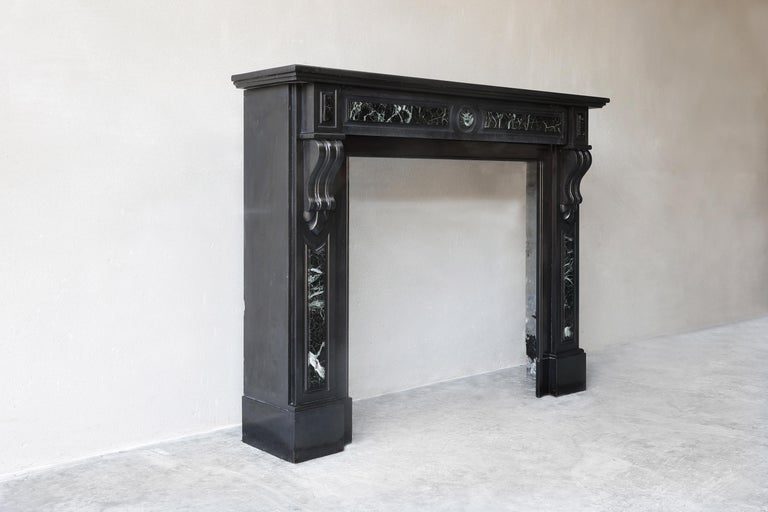 Beautiful ornate fireplace made of Noir de Mazy marble with green verde marble. A beautiful model in terms of size and shape. This fireplace is in Louis XVI style and dates from the 19th century. This type of fireplace fits perfectly in both a